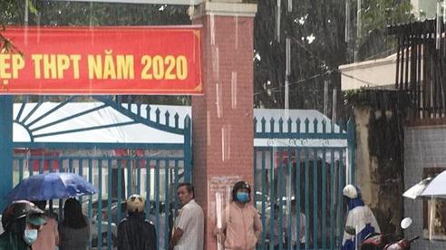 Phụ huynh ở Bình Phước đứng đợi thí sinh dưới cơn mưa lớn trong buổi thi Toán chiều nay