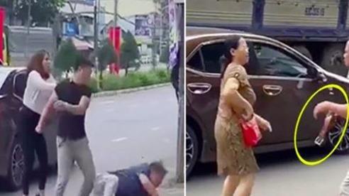 Bị nam thanh niên đánh ngã trên đường, người đàn ông cầm thắt lưng da quật vào ô tô