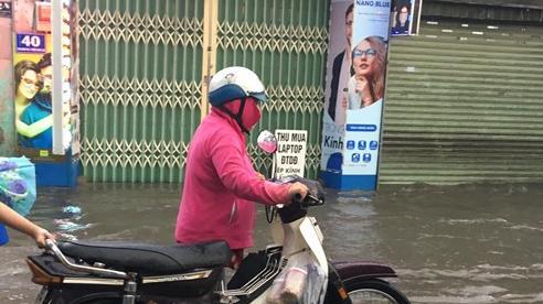 Nhiều tuyến đường ở Sài Gòn lại thành sông sau mưa lớn, các cửa hàng phải đóng cửa vì nước tràn vào nhà