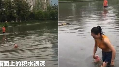 Cô gái Trung Quốc điềm nhiên bơi qua con phố ngập vì sợ đi làm muộn