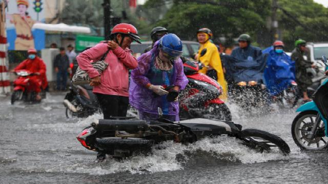 [ẢNH] Nước chảy xiết kéo nhiều xe máy đổ nhào giữa phố Sài Gòn, người dân dắt bộ cho an toàn