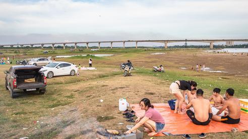 Bãi bồi dưới chân cầu Vĩnh Tuy trở thành nơi sống 'chill' hot nhất vào lúc này của người Hà Nội, được bắt ốc, nướng cá, bay dù lượn, cái gì cũng có!
