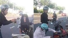 Thấy 2 mẹ con loay hoay dắt xe máy giữa trưa nắng, nam thanh niên có hành động khiến nhiều người ấm lòng