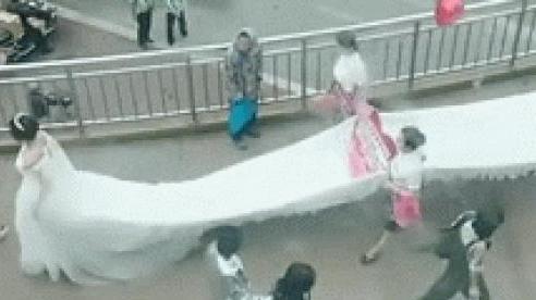 Choáng với chiếc váy cưới dài cả trăm mét, phủ nguyên cây cầu cũng không hết phải huy động hàng chục người nâng váy cho cô dâu!