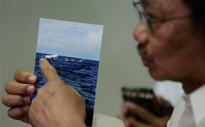 Bộ trưởng Nông nghiệp Philippines Emmanuel Pinol shows a June 10 photo of the damaged Filipino fishing boat F/B GEM-VER after it was hit by a Chinese vessel at the Recto bank during a press conference on June 17, 2019.