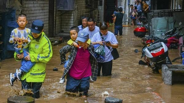 Trẻ em được giải cứu trong cơn đại hồng thủy đang reo rắc tai họa đến nhiều tình ở Trung Quốc.