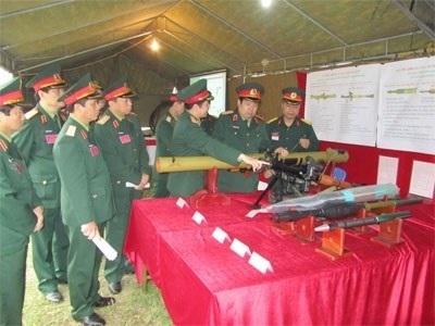 Nguyên Bộ trưởng Bộ Quốc phòng Phùng Quang Thanh kiểm tra súng chống tăng RPG-29 cùng các loại đạn chống tăng, diệt bộ binh thế hệ mới do Việt Nam tự sản xuất. Ảnh: QĐND.