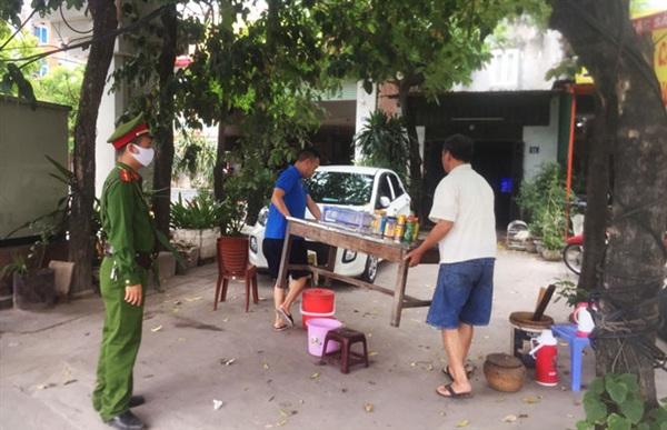 Công an phường Hoàng Liệt (quận Hoàng Mai) nhắc nhở người dân thu dọn hàng quán ở vỉa hè.