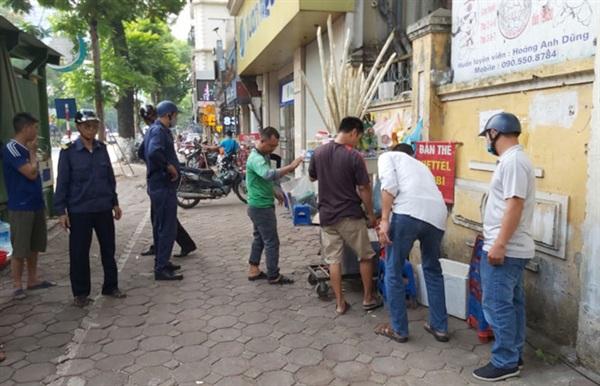 Lực lượng chức năng phường Điện Biên (quận Ba Đình) xử lý các trường hợp bán hàng trên vỉa hè phố Nguyễn Thái Học.