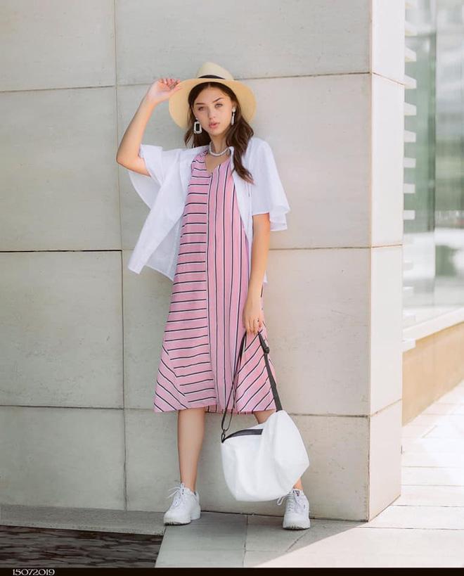 Khi dạo phố, nữ người mẫu 20 tuổi trẻ trung, năng động với váy suông, giày sneaker.