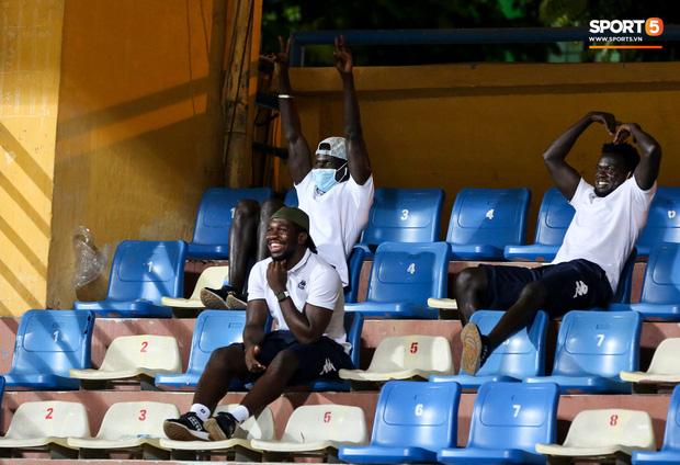 Không chỉ ăn mừng với các đồng đội dưới sân, Minh Dĩ còn nhận được sự tán dương của các ngoại binh đang xem trận đấu trên khán đài. Rimario (hàng dưới) cười rất tươi khi thấy người đồng đội trẻ lập công, liên tục gọi 'Dĩ! Dĩ! Dĩ'. Trong khi đó, Moses (phải) làm hình trái tim còn Pape Omar giơ tay thể hiện chiến thắng