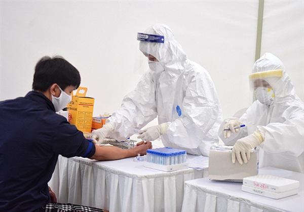 Nhân viên y tế lấy mẫu máu xét nghiệm Covid-19 cho bệnh nhân - Ảnh: Ngô Nhung