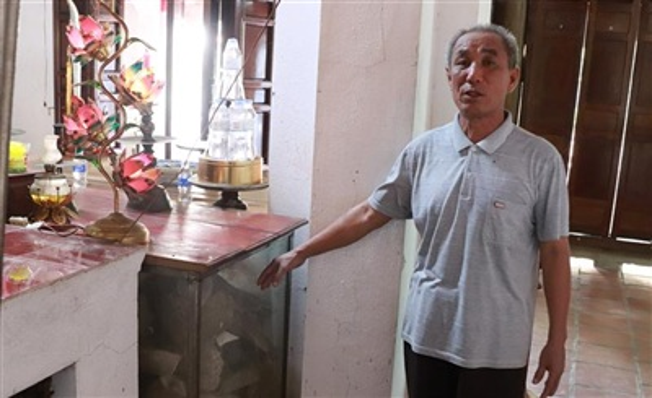 Ông Hoàng Văn Ngoan, người trông coi đền cá Ông kể về nguồn gốc bộ xương cá voi. Ảnh: Thanh Thuận