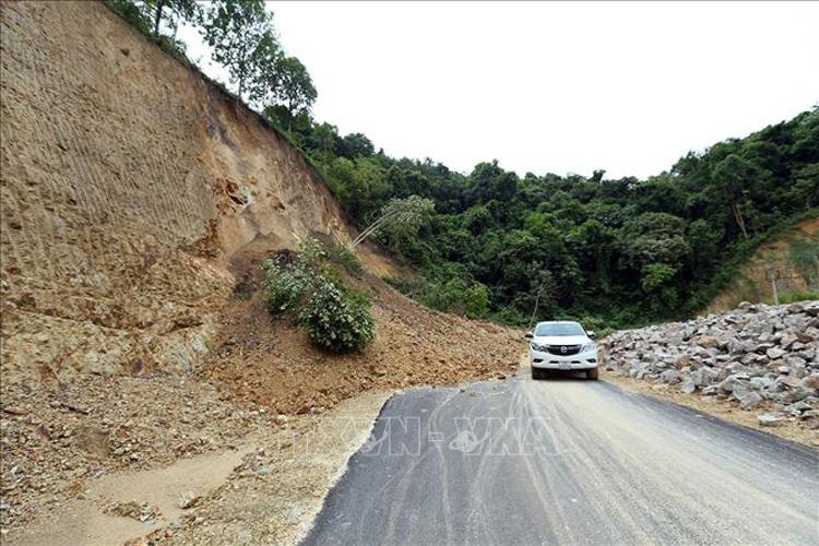 Đoạn đường sạt lở tại Lèng-Mường Phăng (Điện Biên) khiến các xe khó khăn khi di chuyển qua. Ảnh: Phan Tuấn Anh/TTXVN.