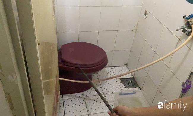 Anh Hiếu dùng cây khều nắp bồn cầu nhà vệ sinh để cho chúng tôi xem nơi từng xuất hiện rắn lớn.