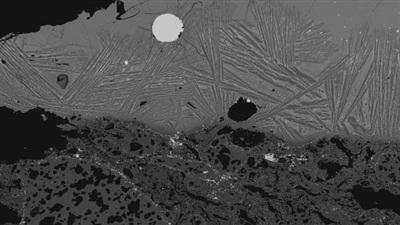 Hình ảnh từ kính hiển vi cho thấy một mảnh thép tròn kẹt trong xỉ