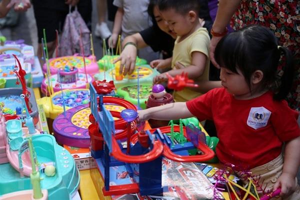 Các em bé thích thú với đồ chơi tại phố Hàng Mã trong Tết Trung Thu. (Ảnh: Hoàng Hiếu/TTXVN)