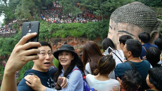 Du khách đến chiêm ngưỡng tượng Phật khổng lồ Lạc Sơn ở tỉnh Tứ Xuyên, Trung Quốc trong kỳ nghỉ lễ quốc khánh năm 2019.