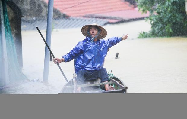Người đàn ông chèo thuyền vội vã, ánh mắt cầu cứu, gọi đội cứu hộ đến cứu người giữa biển nước mênh mông (Ảnh: Vietnamnet)