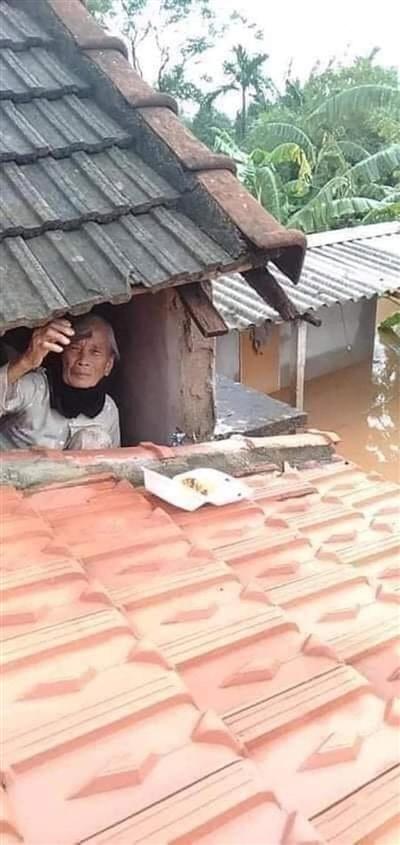Người dân trú trên mái nhà, đợi đội cứu hộ đến tiếp tế lương thực (Ảnh: Page Quảng Trị)