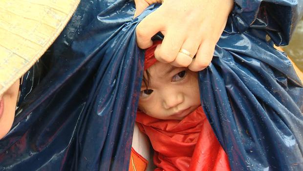 Em bé được cứu hộ tại Quảng Bình, ngồi sợ hãi trong lòng người lớn