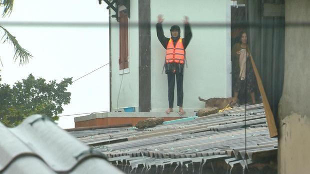 Người đàn ông đứng trên mái nhà vẫy tay gọi cứu hộ