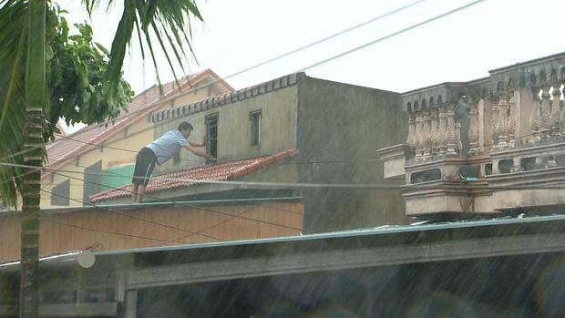 Một người đàn ông khác cũng đứng trên mái nhà gia cố lại nơi trú ẩn của gia đình