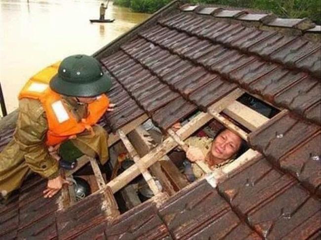 Người phụ nữ được lực lượng chức năng giải cứu từ trên mái nhà. Ảnh: Tiền phong.