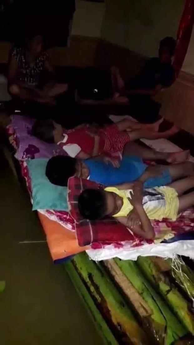 Những đứa trẻ ngủ trên bè chuối, bên dưới là dòng nước lũ. Ảnh: MXH.
