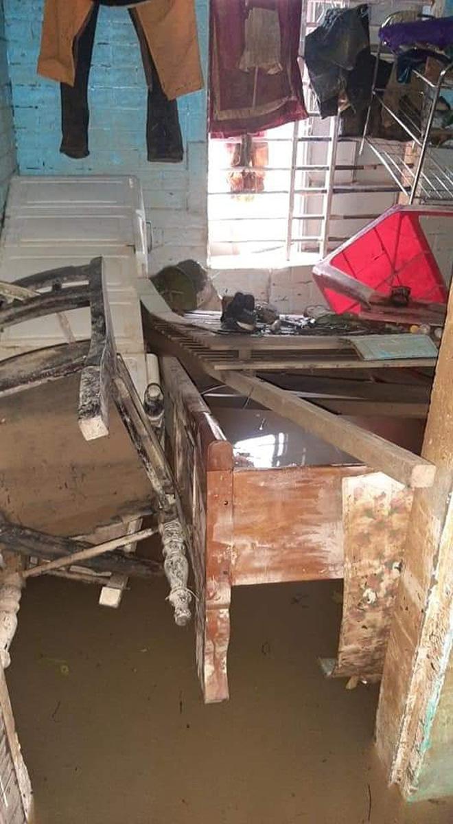 Nước lũ dâng cao khiến đồ đạc trong nhà bị xáo trộn, bàn ghế đổ nghiêng ngả bám đầy bùn đất