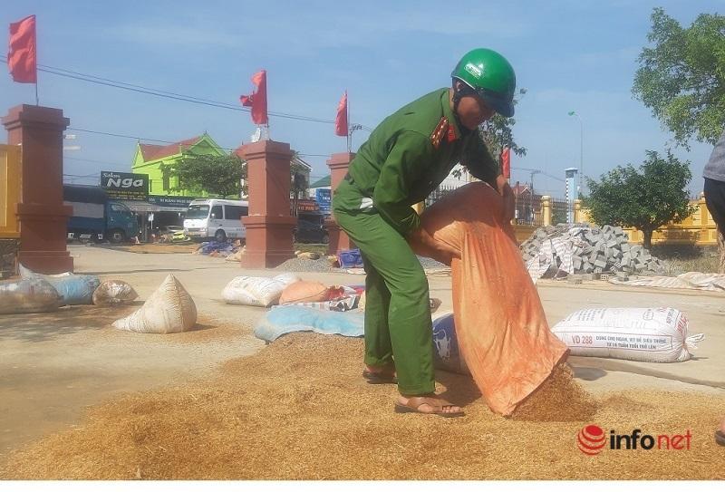 Cán bộ, chiến sĩ công an xã Võ Ninh giúp bà con nông dân phơi lúa.