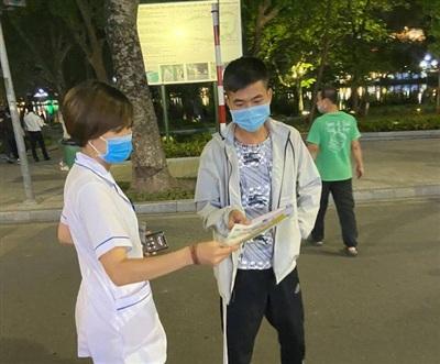 Cán bộ y tế tuyên truyền, nhắc nhở hàng chục người dân nâng cao ý thức phòng chống dịch.