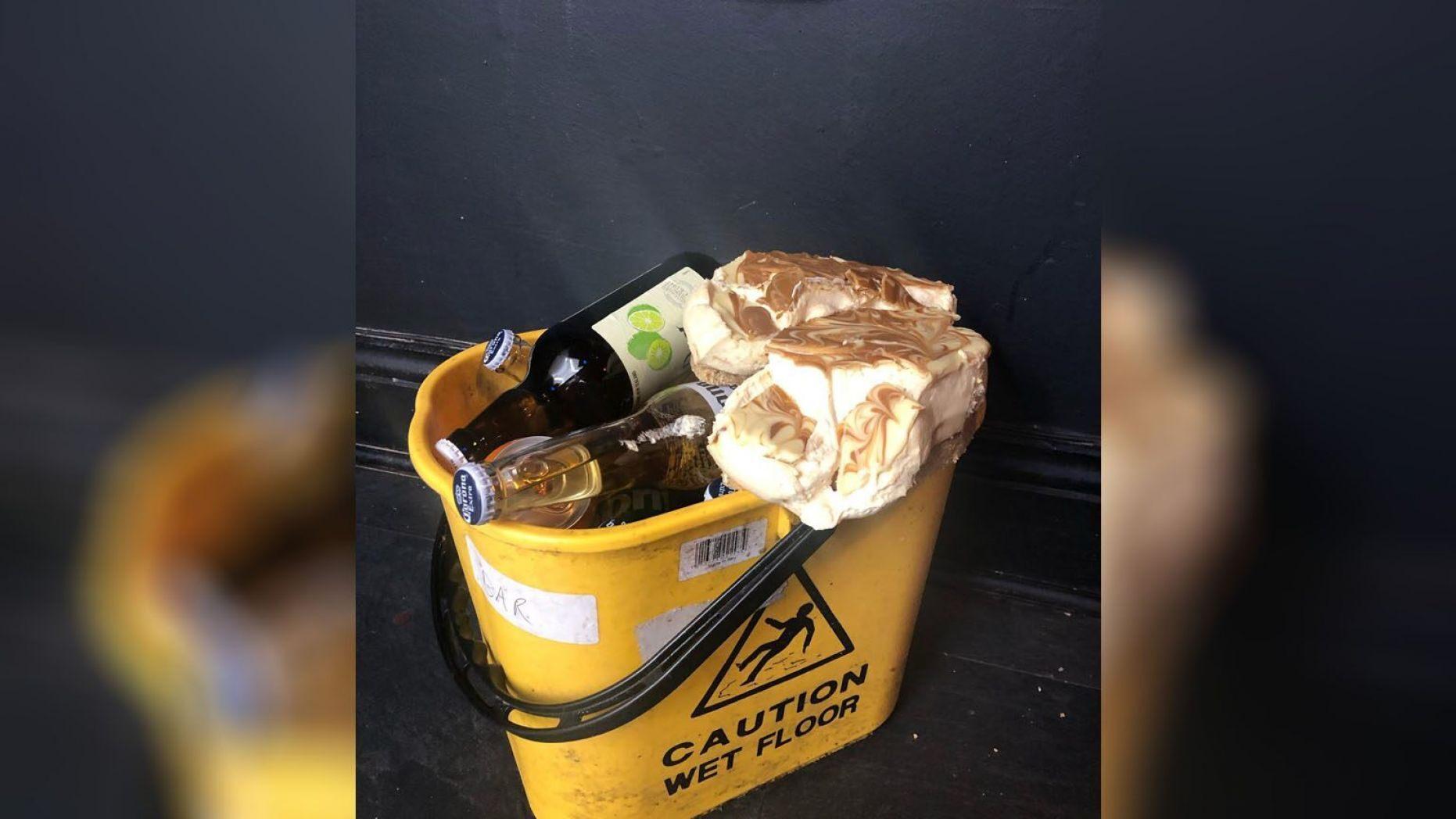 Xô đựng đầy chai rượu bia và bánh pho mát ăn dở đặt bên cạnh tên trộm