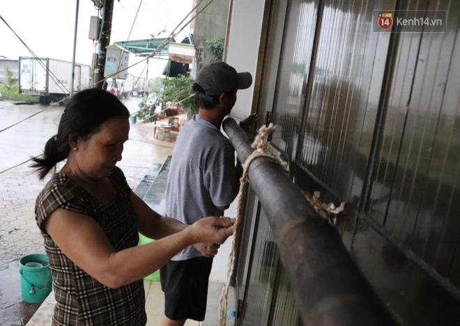 Vợ chồng chú Bốn cột lại nhà trước khi cơn bão số 9 đổ bộ (Ảnh: Văn Tiên)