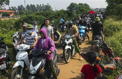 Nghe tin tìm thấy thi thể em Hiền ở đối diện thôn Gia Khánh vào trưa 27/10, hàng nghìn người dân kéo đến đứng chật cứng 2 bên đường theo dõi.