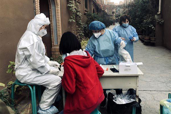 Các nhân viên y tế đang lấy mẫu xét nghiệm Covid-19 cho một học sinh ở Kashgar, Tân Cương hôm 26/10. Amhr: CGTN