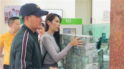 Thủy Tiên và Công Vinh đi rút tiền để phát cho người dân (Ảnh: FBNV)