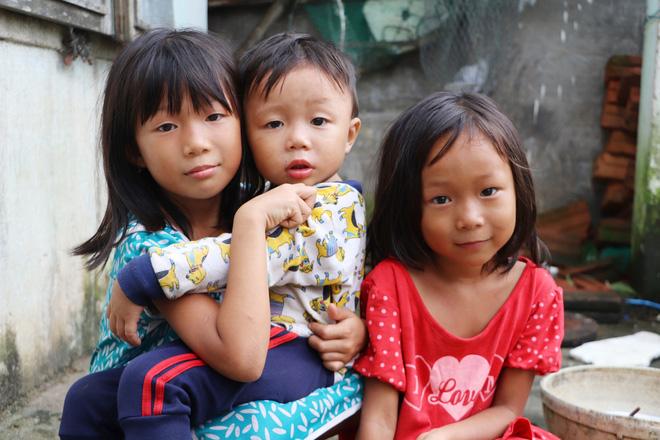 Mấy chị em thay phiên nhau giữ đứa em út để bố mẹ dọn lại nhà cửa