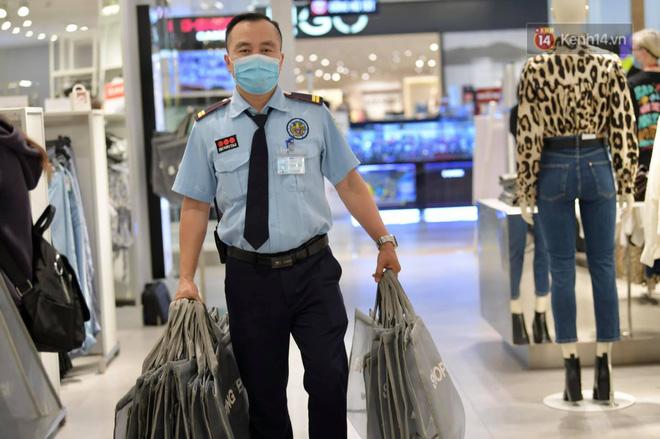 Bảo vệ của gian hàng liên tục phải mang giỏ để hàng cho hành khách từ quầy thanh toán ra ngoài do lượng khách bắt đầu tăng (Ảnh: Phương Thảo)