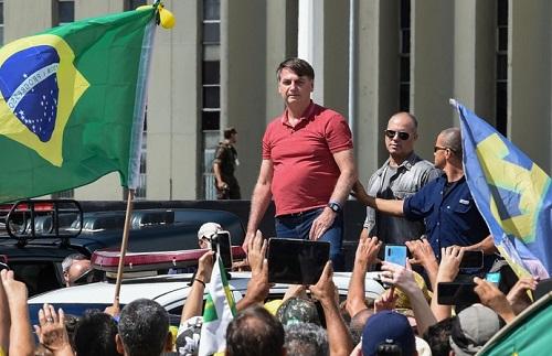 Tổng thống Brazil Jair Bolsonaro (áo đỏ) trong một cuộc biểu tình phản đối các biện pháp phong tỏa để ngăn chặn COVID-19. Ảnh: AFP