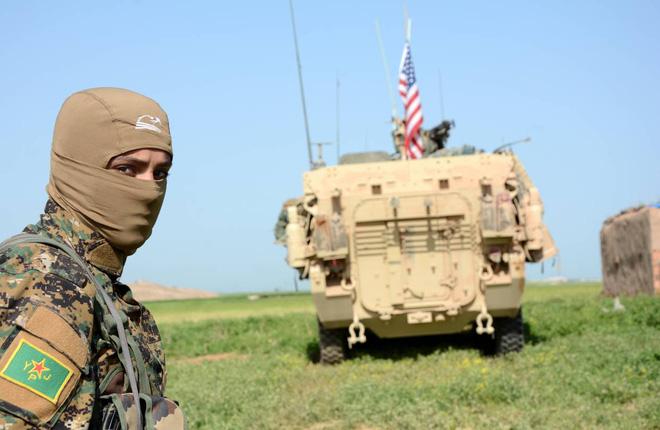Một tay súng thuộc YPJ (Đơn vị bảo vệ phụ nữ người Kurd) phía sau xe bọc thép của Mỹ.
