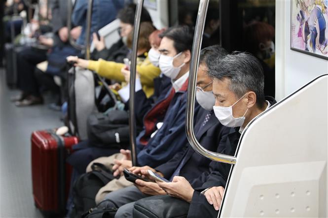Người dân đeo khẩu trang phòng lây nhiễm COVID-19 khi đi tàu điện ngầm tại Tokyo, Nhật Bản, ngày 12/11/2020. Ảnh: THX/ TTXVN