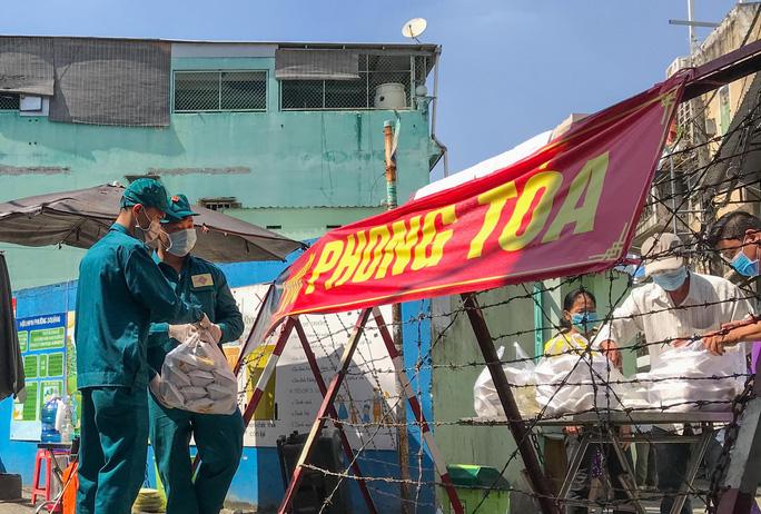 'Tiếp tế' thực phẩm cho người dân tại điểm phong tỏa ở quận 6 - ảnh: HOÀNG TRIỀU
