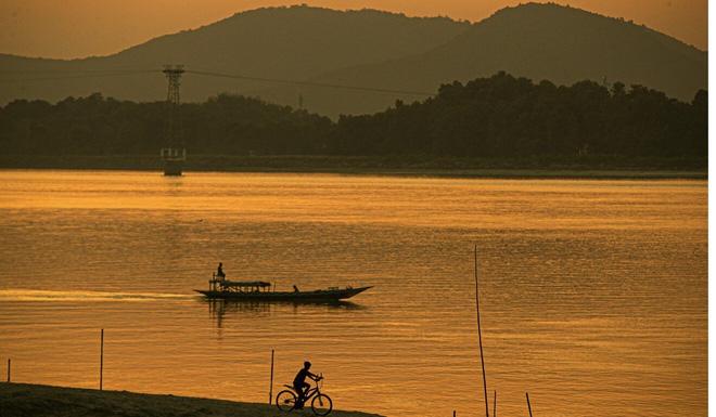 Cậu bé đạp xe dọc theo sông. Ảnh: AP