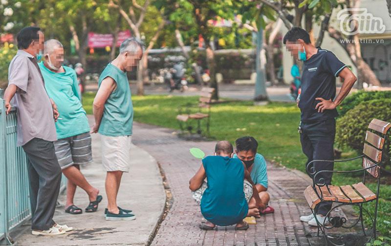 Một số người trung tuổi thậm chí còn bỏ khẩu trang và đứng gần nhau để xem đánh cờ tướng.