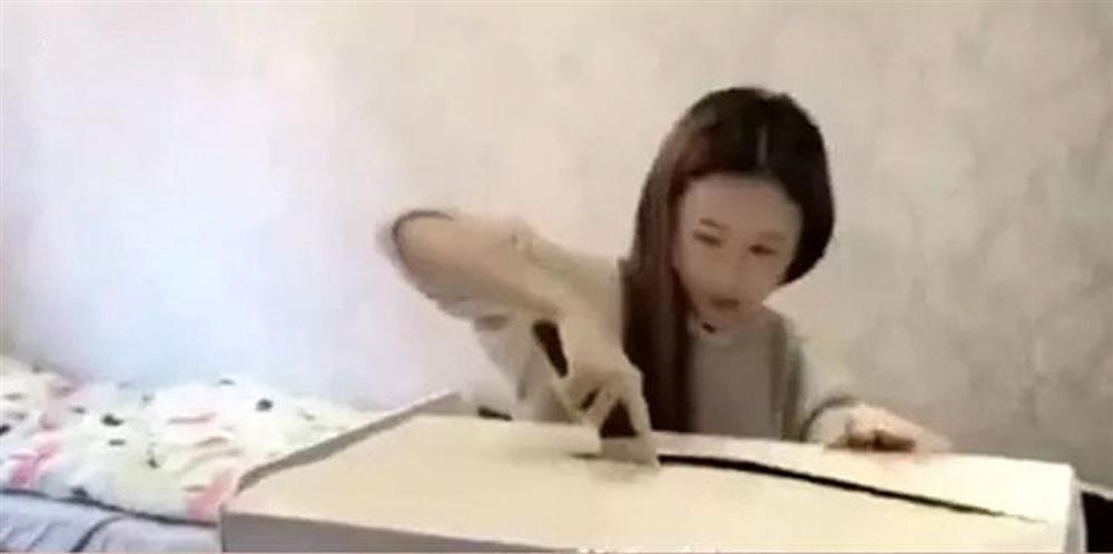 Cô nàng đã dùng con dao sắc rạch rõ sâu để mở hộp quà.