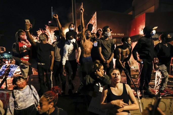 Người biểu tình tập trung ở sở cảnh sát bị đốt cháy tại Minneapolis hôm 28-5. Ảnh: AP