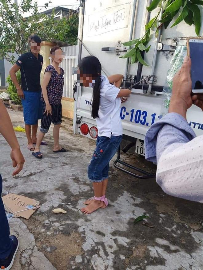 Cảnh bé gái bị cột chân, trói quặt tay vào thùng xe tải. Ảnh: facebook