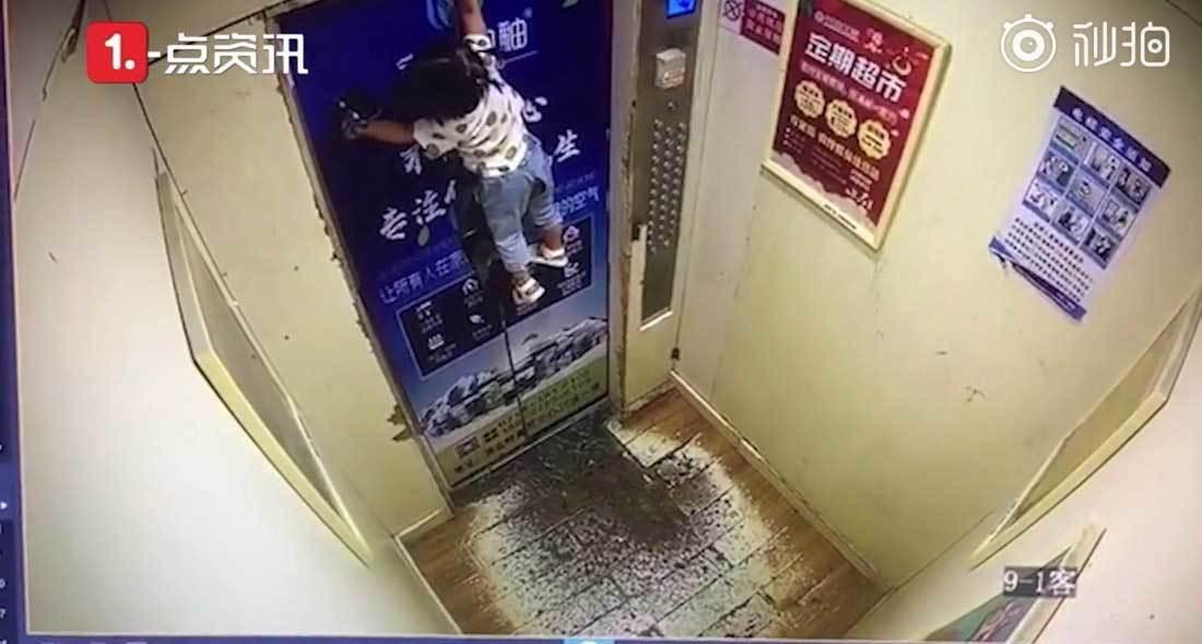Kẹt dây dắt, em bé bị treo lơ lửng ở cửa thang máy (Ảnh: Shanghaiist)