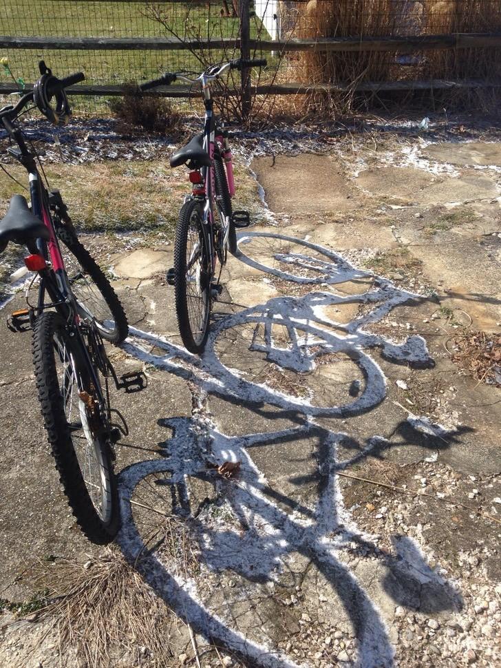 Mặt trời làm tan chảy tuyết trên mặt đất, nhưng lại trừ chỗ bóng cái xe đạp!